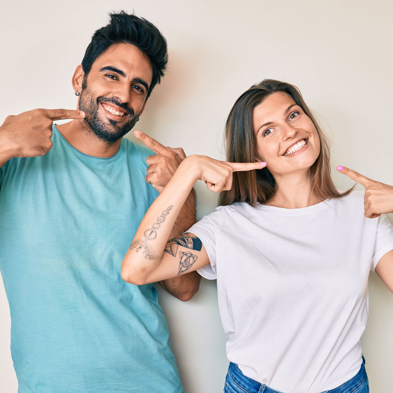 young-couple-smiling-pointing-at-teeth